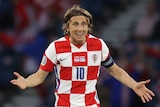 Luka Modric holds his hands up and looks surprised.