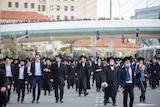 A large group of men in dark suits and hats walk en masse on a city street on a cloudy day.