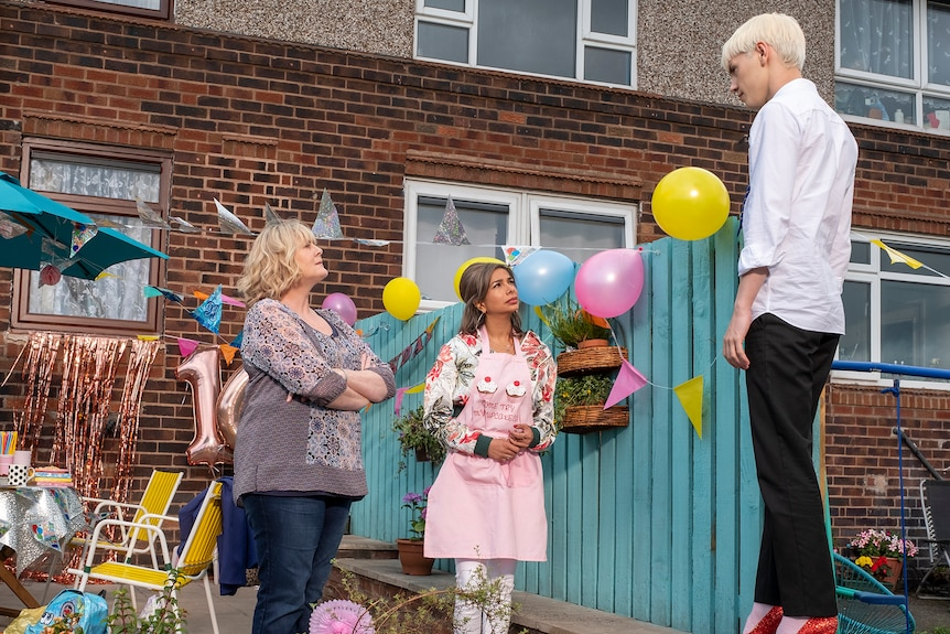 Sarah Lancashire and Shobna Gulati are in a garden filled with party decorations looking at Max Harwood in glittery red heels.