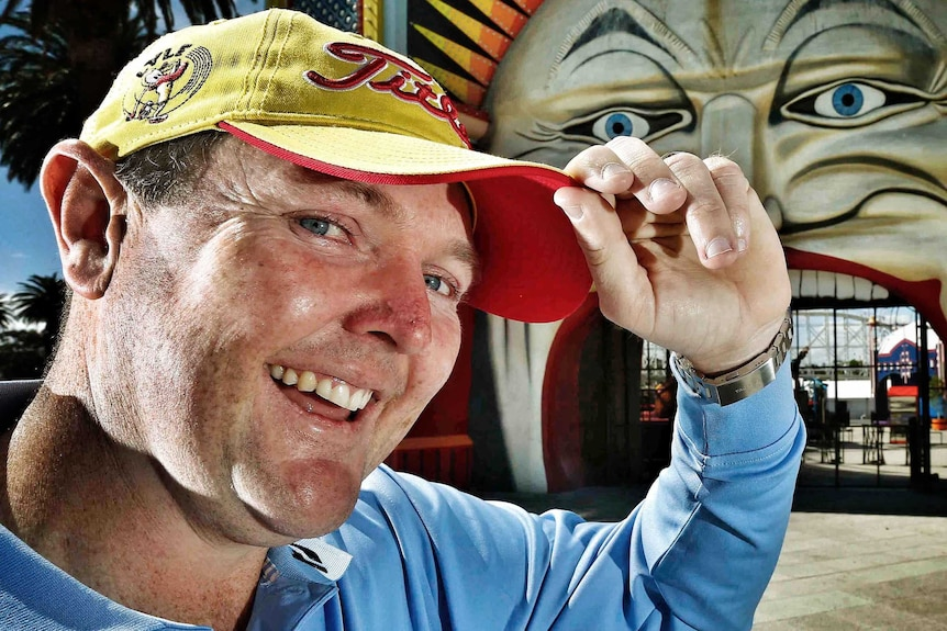 Jarrod Lyle smiles and tips his hat with the entrance to Luna Park in the background