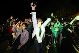 People celebrate at night in the outdoors.