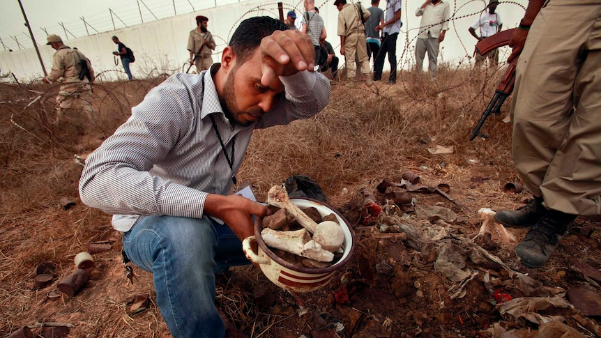 A man collects human remains at the site of a mass grave in Tripoli