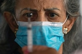 A older woman wearing a face mask eyes a syringe held in front of her face.
