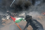 Palestinian demonstrators run for cover holding flags and with black smoke filling the air.