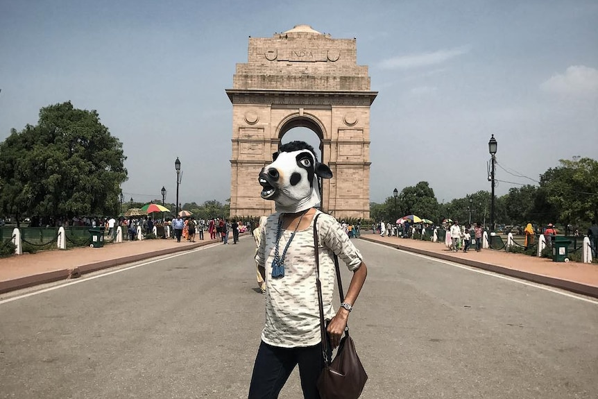 A woman stands on a boulevard wearing a cow mask in front of New Delhi's India Gate.