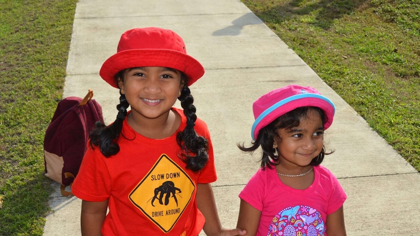 Two young girls wear t-shirts and hats.
