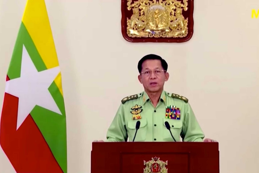 A man in a light green military uniform looks into the camera as he speaks behind a lectern with the Myanmar flag to his right.