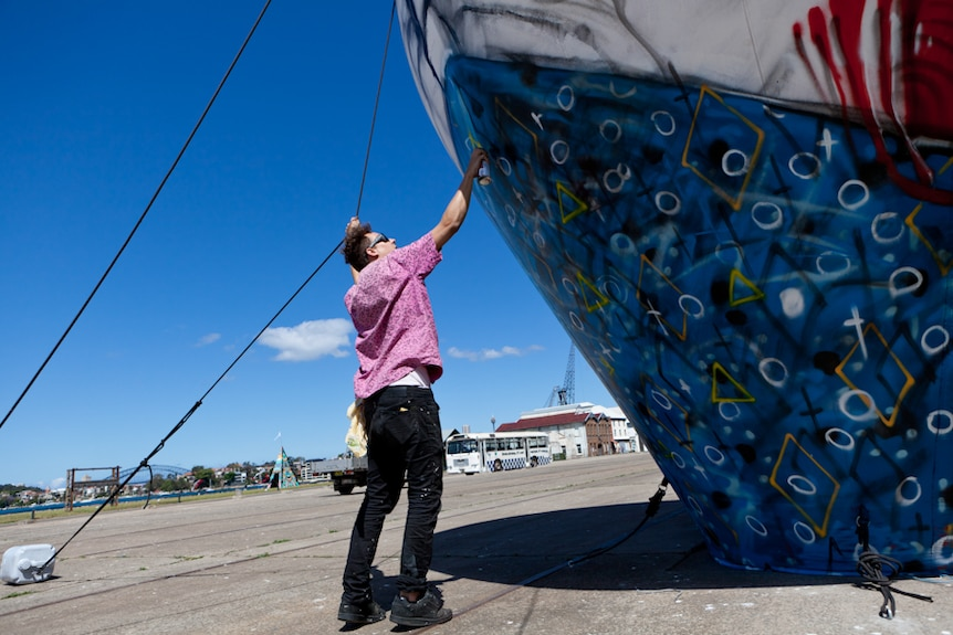 Street artist Anthony Lister at work on Sydney's Cockatoo Island as part of the Outpost street art festival.