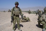 A soldier in Afghanistan wearing army uniform and holding a weapon.