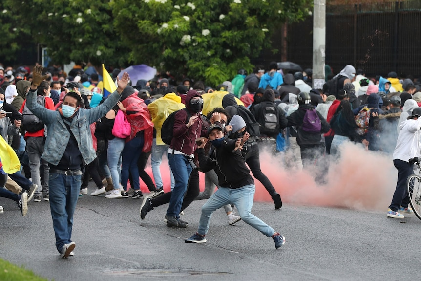A man throws an object towards police as protesters clash with authorities in the street.