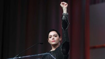 Rose McGowan stands in front of a microphone with her fist held aloft