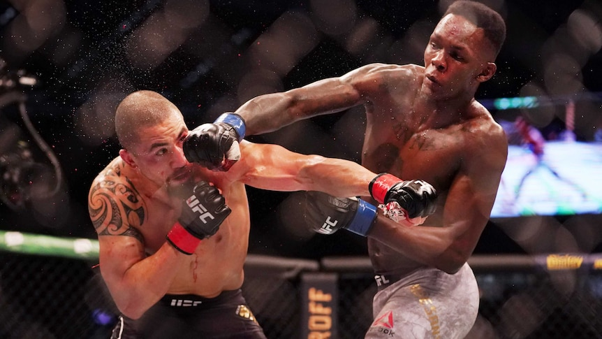 Robert Whittaker gets punched in the head by Israel Adesanya