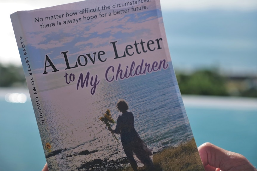 Book front cover, A Love Letter to My Children, photo of Eve with back to the camera, holding sunflowers, ocean behind.