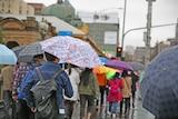 People walking under umbrellas in Melbourne.