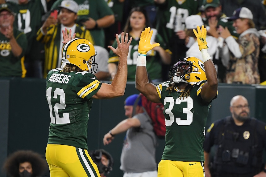Arron Jones and Aaron Rodgers hold their hands up above their heads
