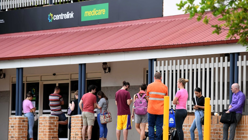 People are seen in a long queue outside a Centrelink office