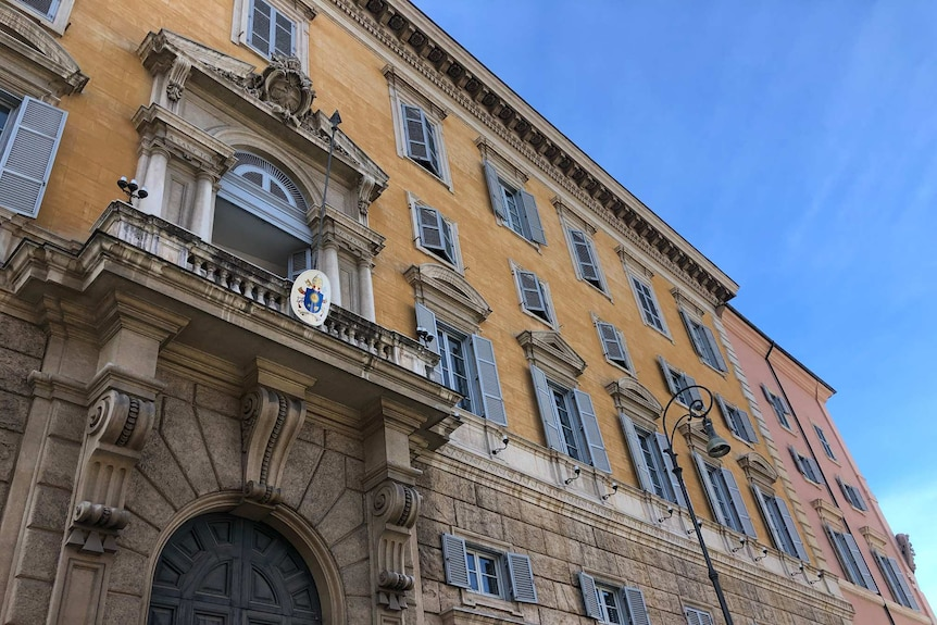 The outside of an ornate building in the Vatican, against a bright blue sky.