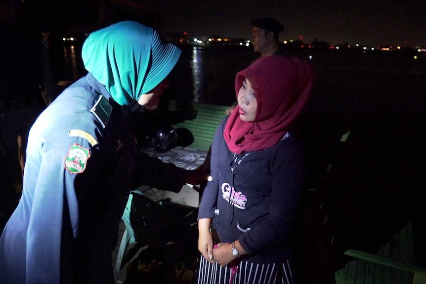 A female officers interviews a woman on the street at night