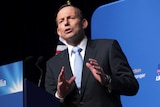 Former prime minister Tony Abbott stands at  a lecturn.