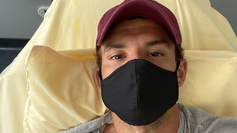Tennis player Grigor Dimitrov wears a mask while lying in bed and flashing a peace sign.