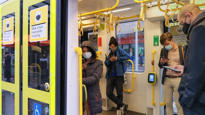 Four commuters wearing masks on a Melbourne train who are looking at their phones through the open door.