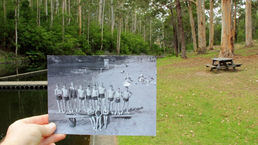 A hand holds a black and white picture of children with a park in the background.