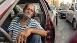 A man sits in his car with a striped shirt on while waiting in line for petrol in Beirut.