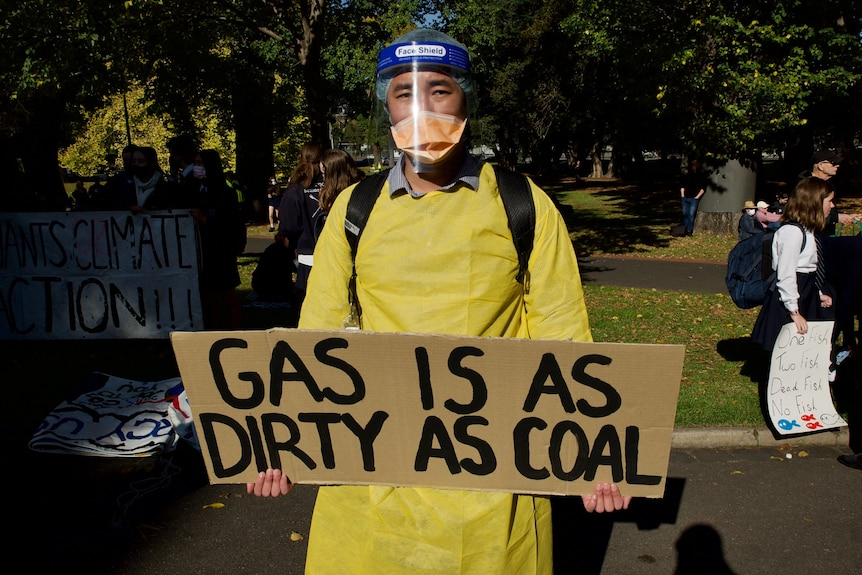 A protester at a climate change rally in Melbourne wears full PPE and holds an anti-gas sign.