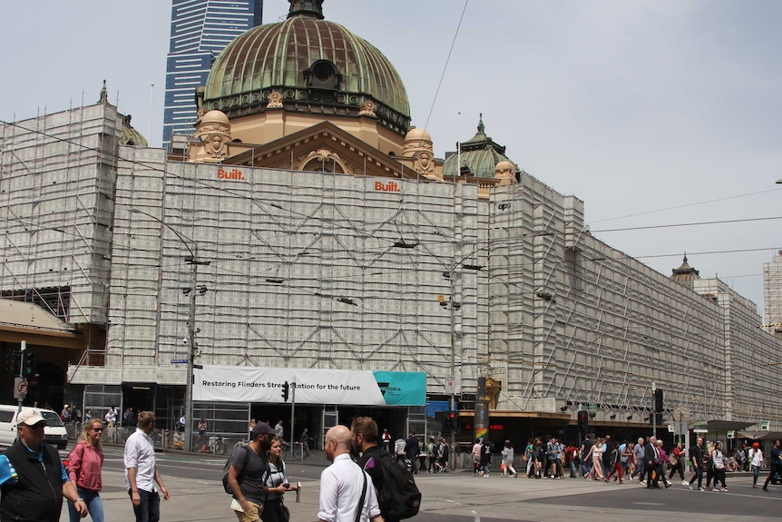 Pedestrians cross in front of a large historic building with a domed roof, the front covered in scaffolding.