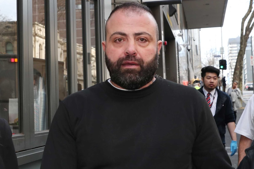 A man in a black jumper, with a beard, walks outside court.
