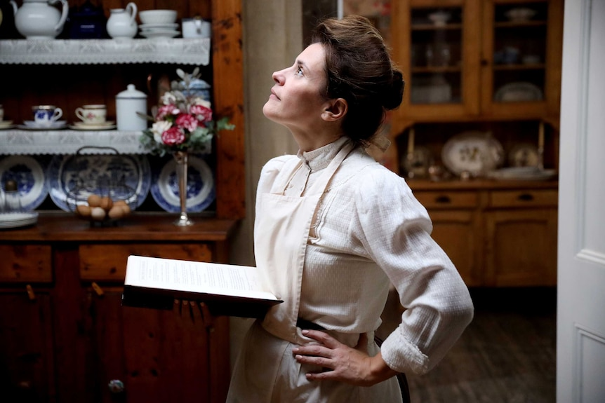 A woman in 1900s dress and an apron looks up from her cook book in contemplation