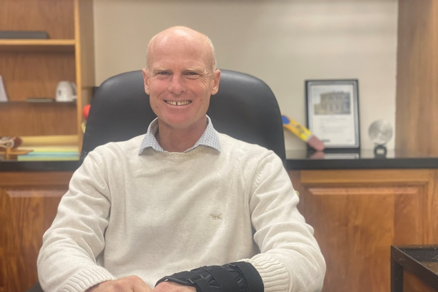 Man sits in chair smiling at camera