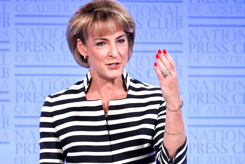 Michaela Cash raises her left hand as she addresses the audience at the National Press Club.