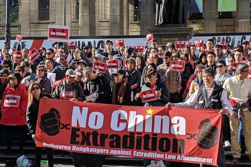 """Thousands of people stand in a city street holding signs that reads """"No China Extradition""""."""