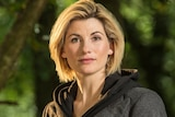 A blonde Jodie Whittaker stands in the woods while removing her hoodie.
