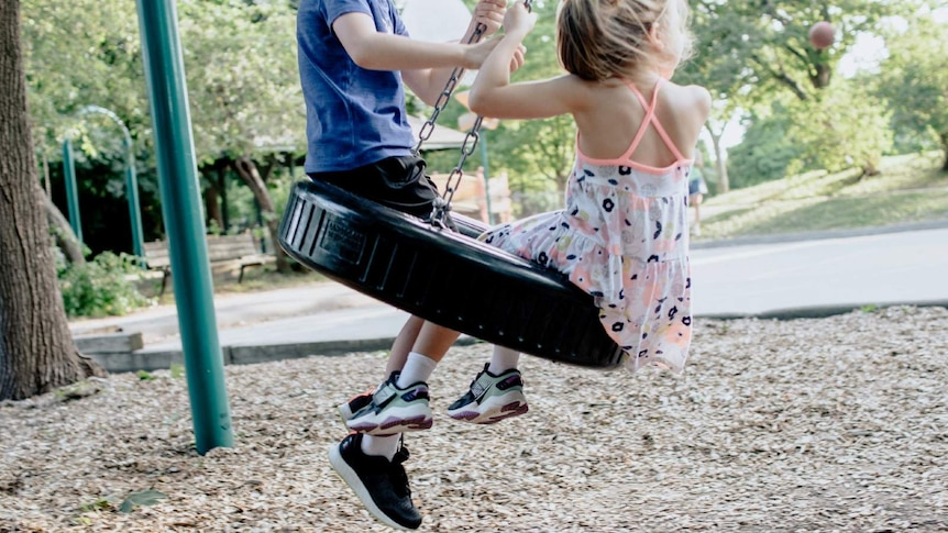 Two kids play on a swing.