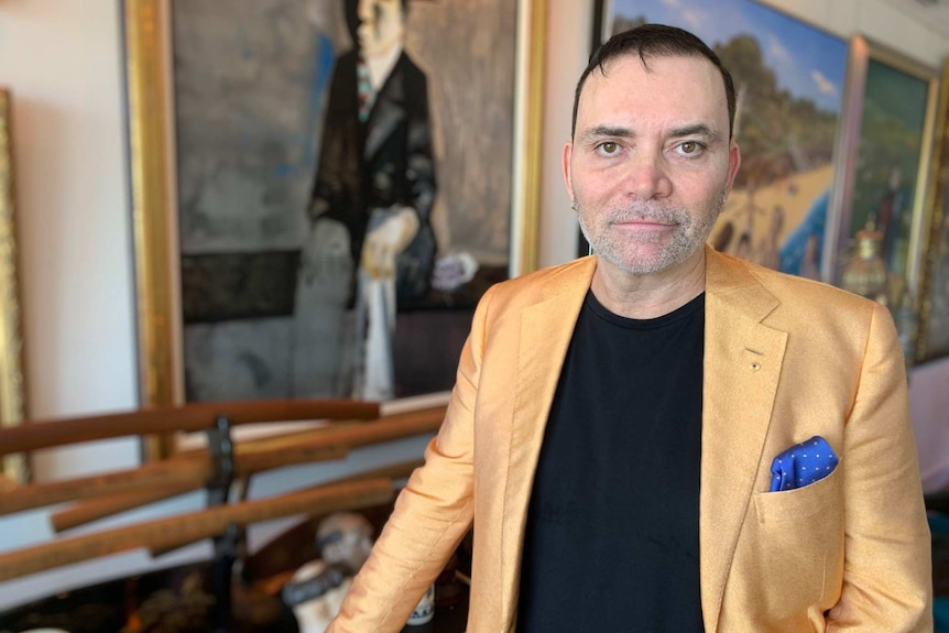 a man in a yellow jacket standing in front of a row of paintings