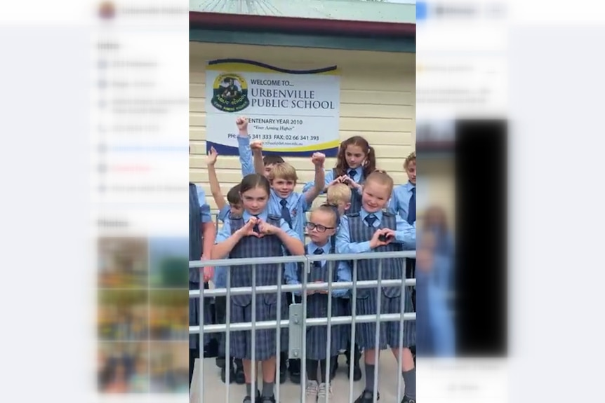 A screen shot of a Facebook video with school children in front of a school sign