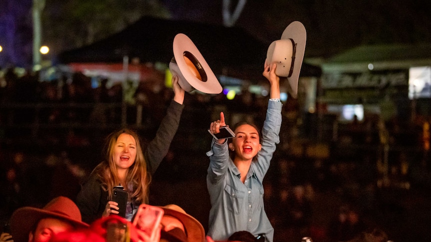 Two girls sitting on someones shoulders rise above a concert crowd waving cowboy hats