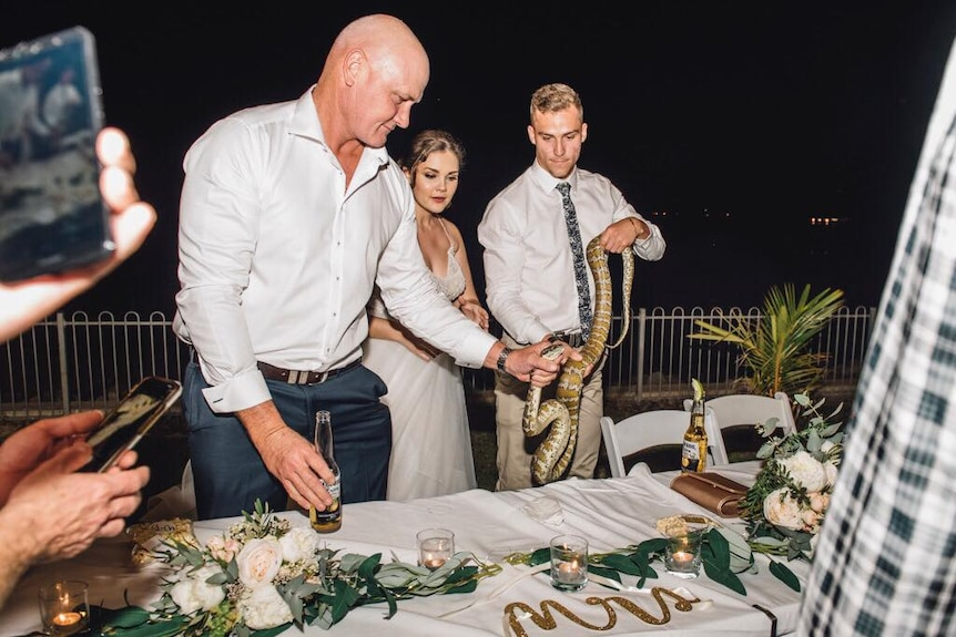 Bridal party guests around table holding snake toward camera.