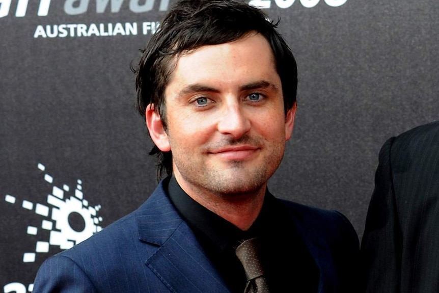 A smiling Daniel Houghton poses for a photo on the red carpet at the 2008 AFI awards in a blue suit and black shirt.