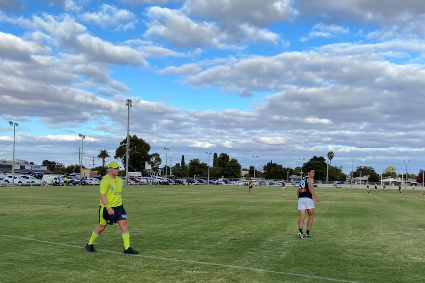 A boundary umpire and a player near the boundary line during a country football game.