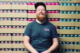 Man sitting in front of canned beer.