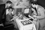 A black-and-white archival photo shows men and women in 1950s formal attire sitting on an aircraft eating from a luxury buffet