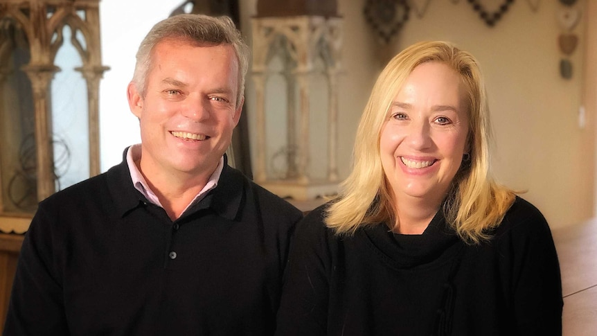 A man and woman sit side by side smiling