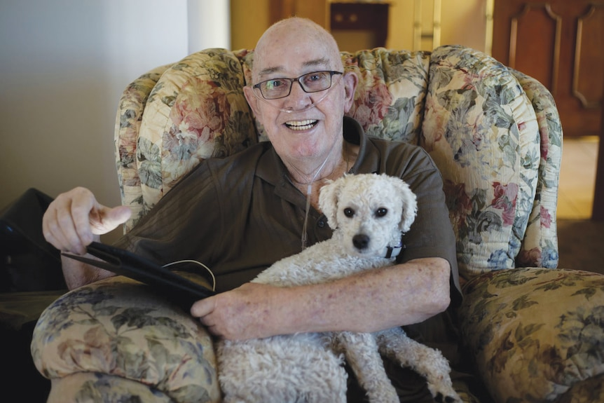 Older man sits with a small white dog on his lap in a floral armchair.