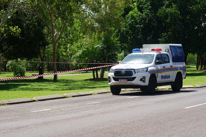 A NT Police car is parked on a street near police tape.