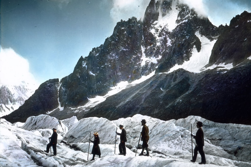 Four men and a woman, all dressed in old-fashioned clothes, hike across a glacier with a snow-topped mountain in the distance.