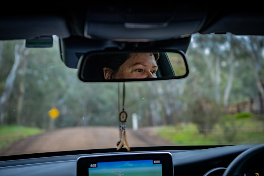 Heidi is seen in the rear view mirror as she drives along a tree-lined, rural road.
