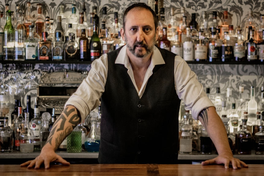 A man wearing a black vest over a white shirt stands in front of a bar with bottles in the background
